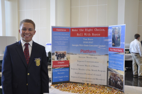"""Student Royce Dickerson stands proud beside his poster displaying his campaign, smartly titled """"Roll With Royce""""."""