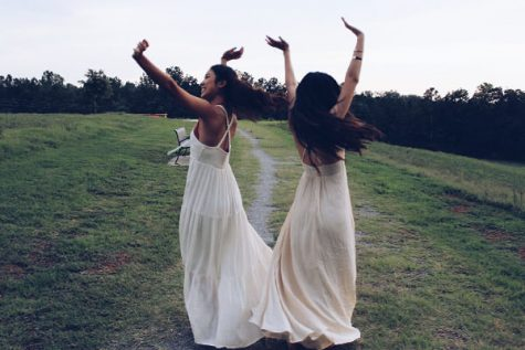 Pre-homecoming antics dictate that these girls spin around in their flowing dresses and loose hair.