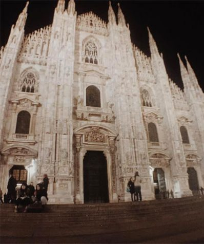The Duomo Milano stands pale and white against the backdrop of the crisp, black winter night in Milan, Italy.