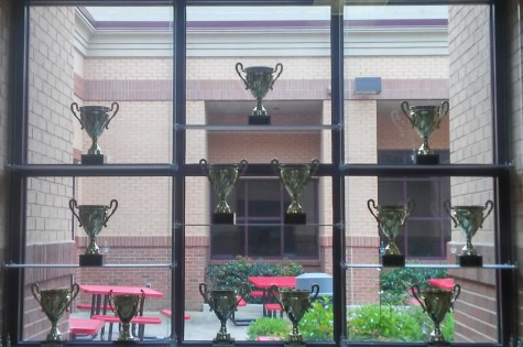 Trophy case featured from the main hallway of Lambert High School, with a courtyard backdrop