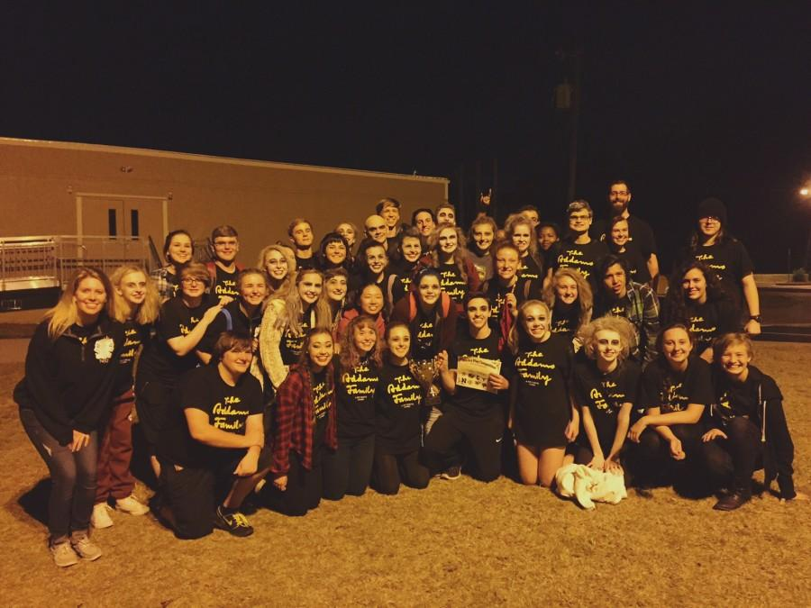 The cast and crew of The Addams Family along with both directors Ms. Carly Berg and Mr. Ryan Wason stand proudly with trophy in hand to celebrate the win.