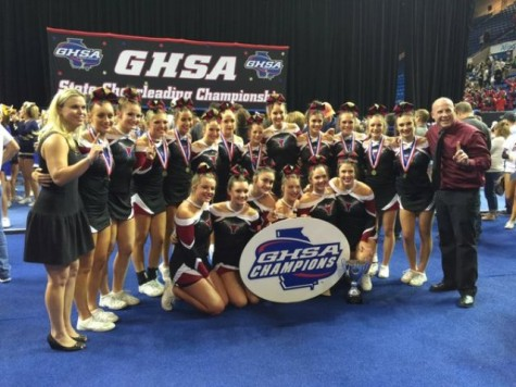 The varsity competition cheerleading team celebrating their state-wide win.
