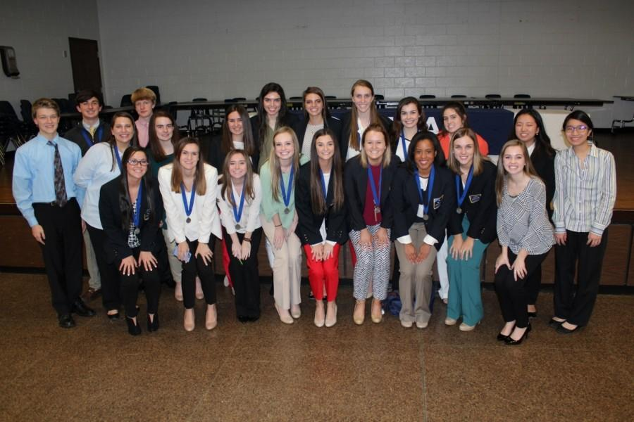 DECA team smiles proudly after serving up a huge dose of Lambert pride at the DECA region competition.