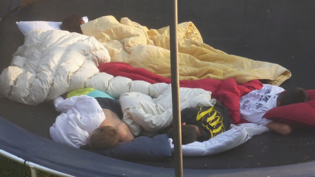 Kids sleeping together on a trampoline.
