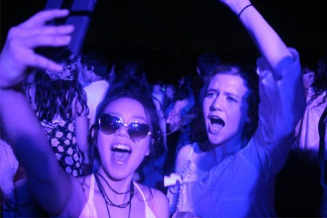 Under the black lights on the practice field, students dance to the classic hit: