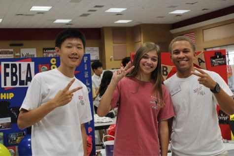Georgia FBLA President Royce Dickerson and fellow FBLA members, Henry Xuan and Jessie Bowman, smile at the camera right before the freshmen flooded the cafeteria.