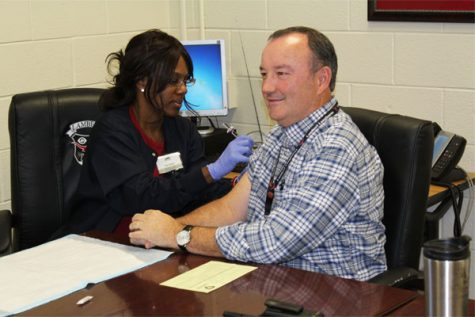 Nurse Conni Springer administers an immunization shot to one of Lambert's staff.