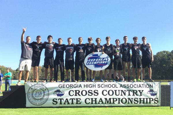 The Lambert boys cross country celebrates their state title win on top of the podium