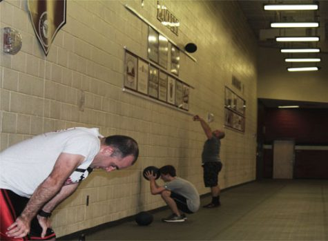 The cross-fit club members, including the coaches, work hard to keep up with their own pace in successfully performing through each exercises.