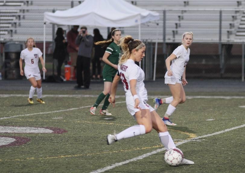 Maddie Eddleman kicks passes the ball ahead during a home game