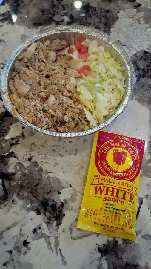 A chicken and rice platter from the Halal Guys with their signature tahini (white) sauce.