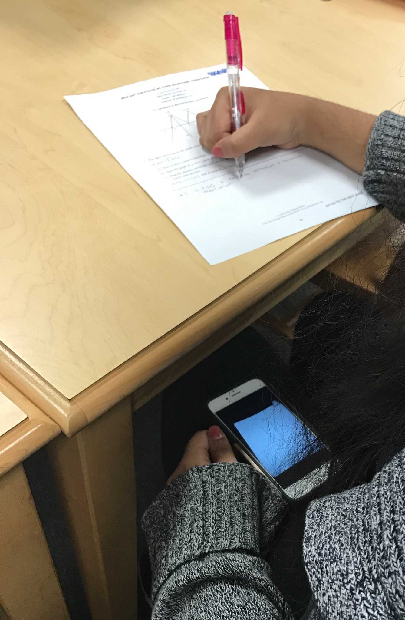 Student cheats on a test by using her phone that has pictures of the answers.