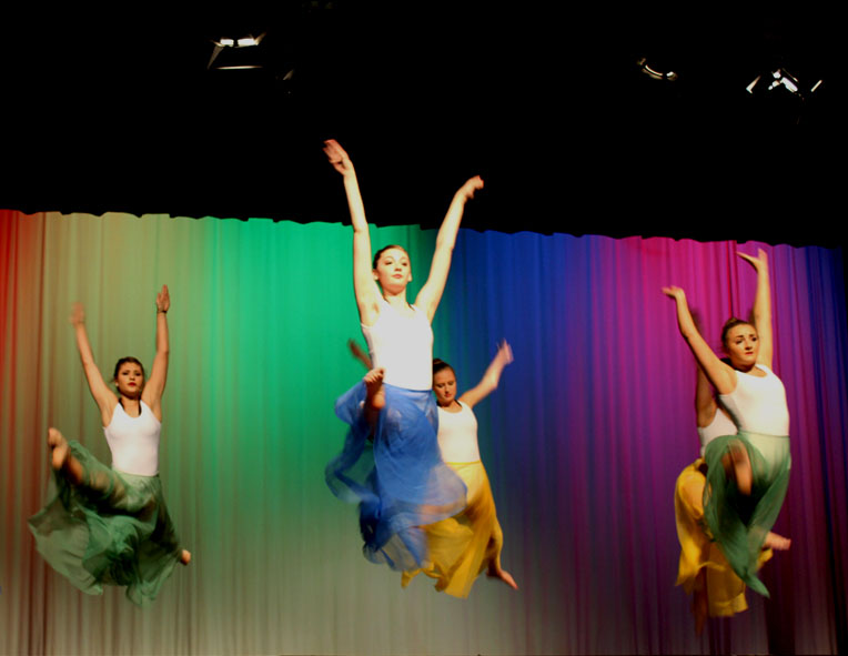 In the dance ROYGBIV, the company performs grand jetés in flowing dresses.