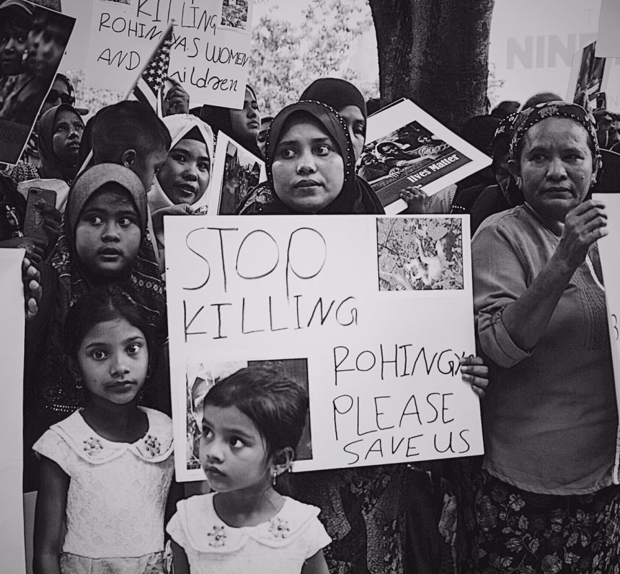 Protesters against the genocide in Myanmar hold signs.
