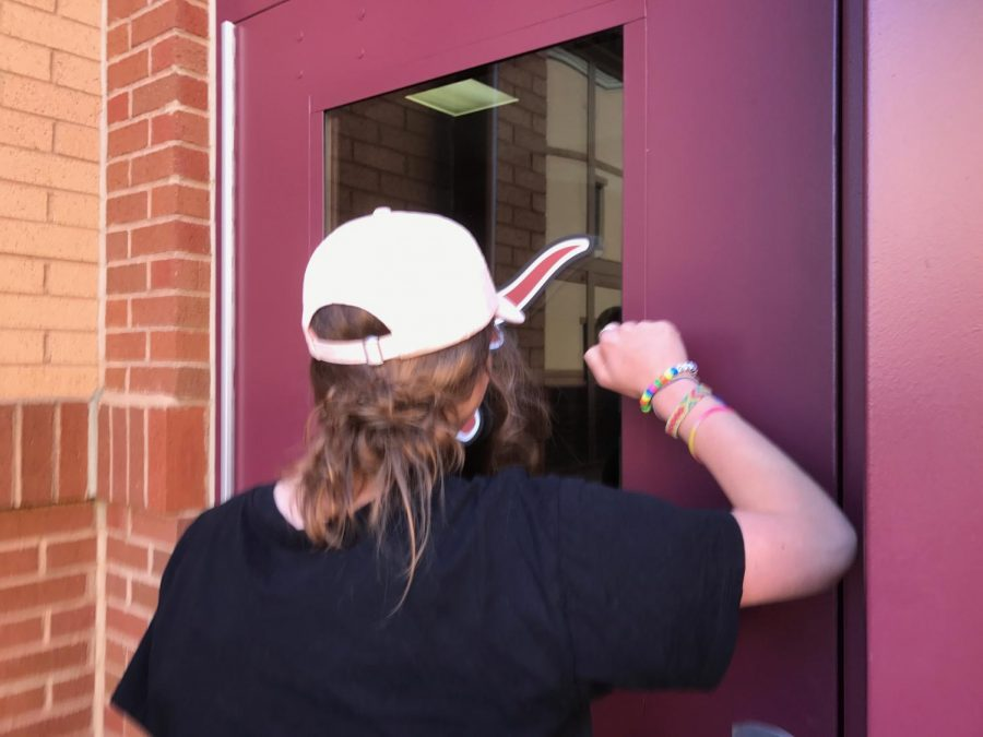 A Lambert student encounters a locked door while trying to enter the school building and must wait for someone inside to hear her knocking.
